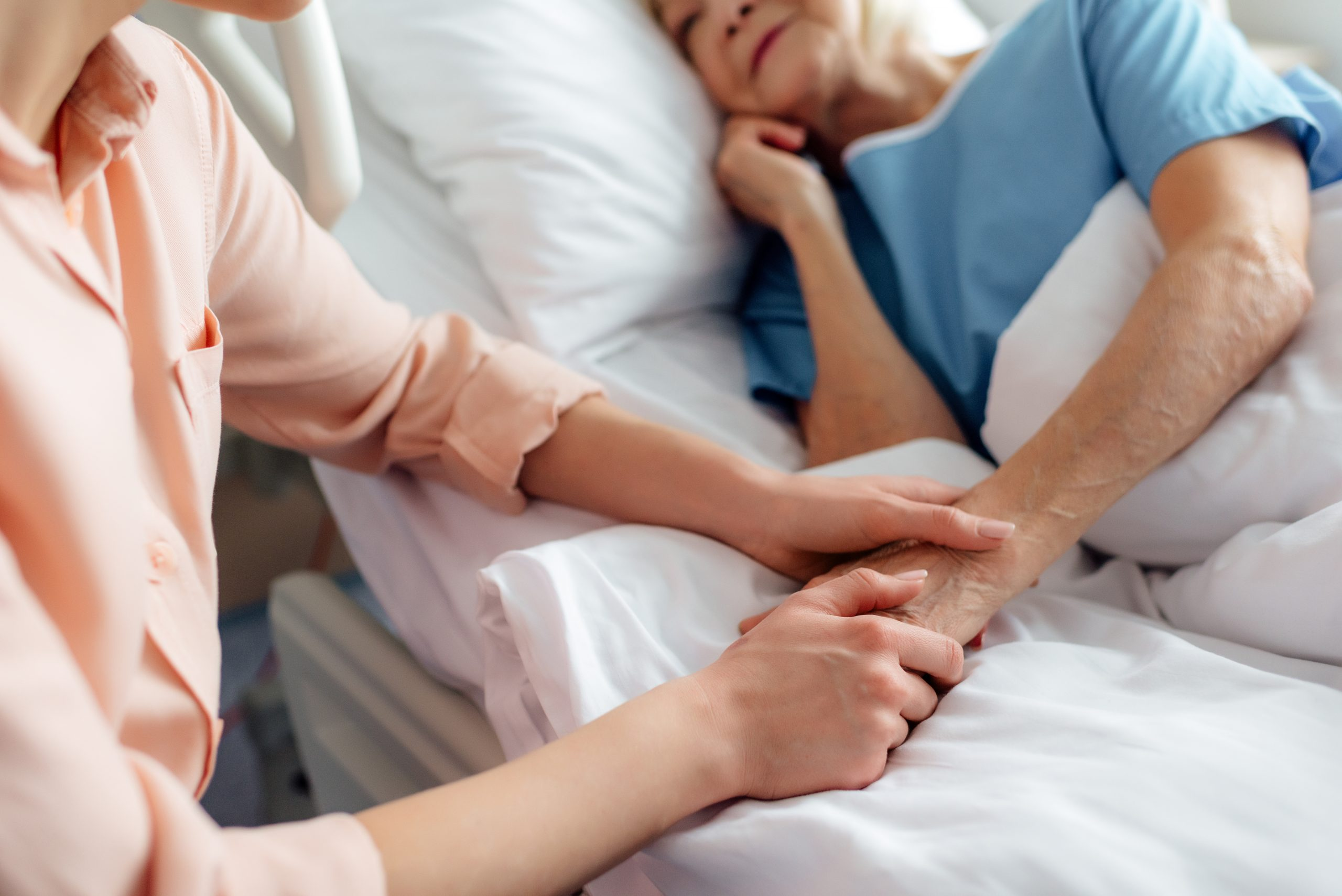 cropped view of daughter sitting near senior mother in bed and holding hands in hospital